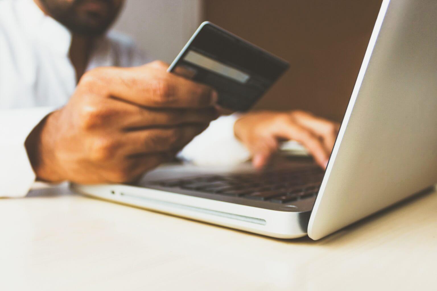 Man enter his credit card using laptop